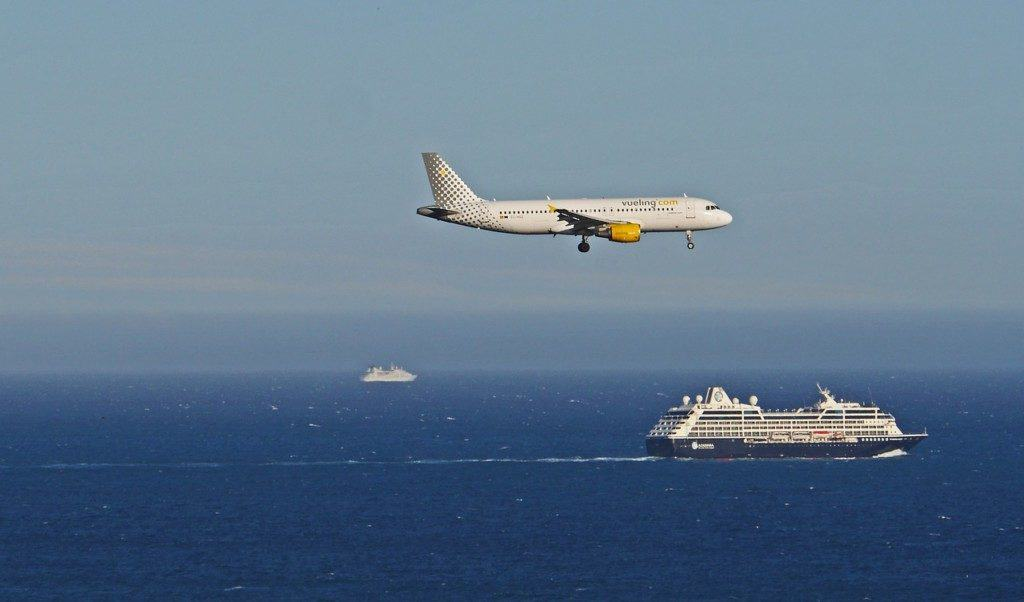 Veuling plane landing with a cruise ship in the background